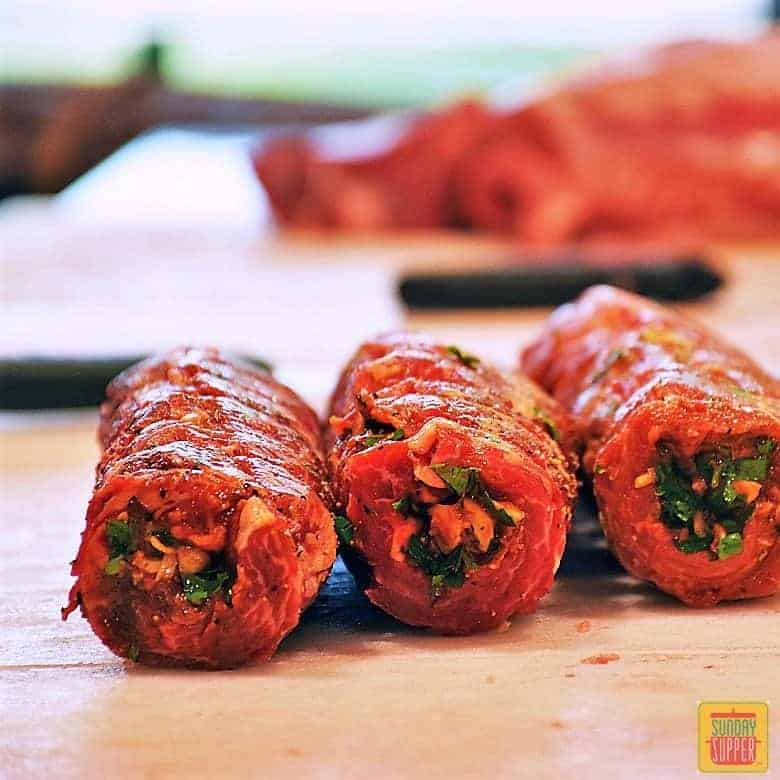 Three rolls of harissa beef roulade on a wooden surface