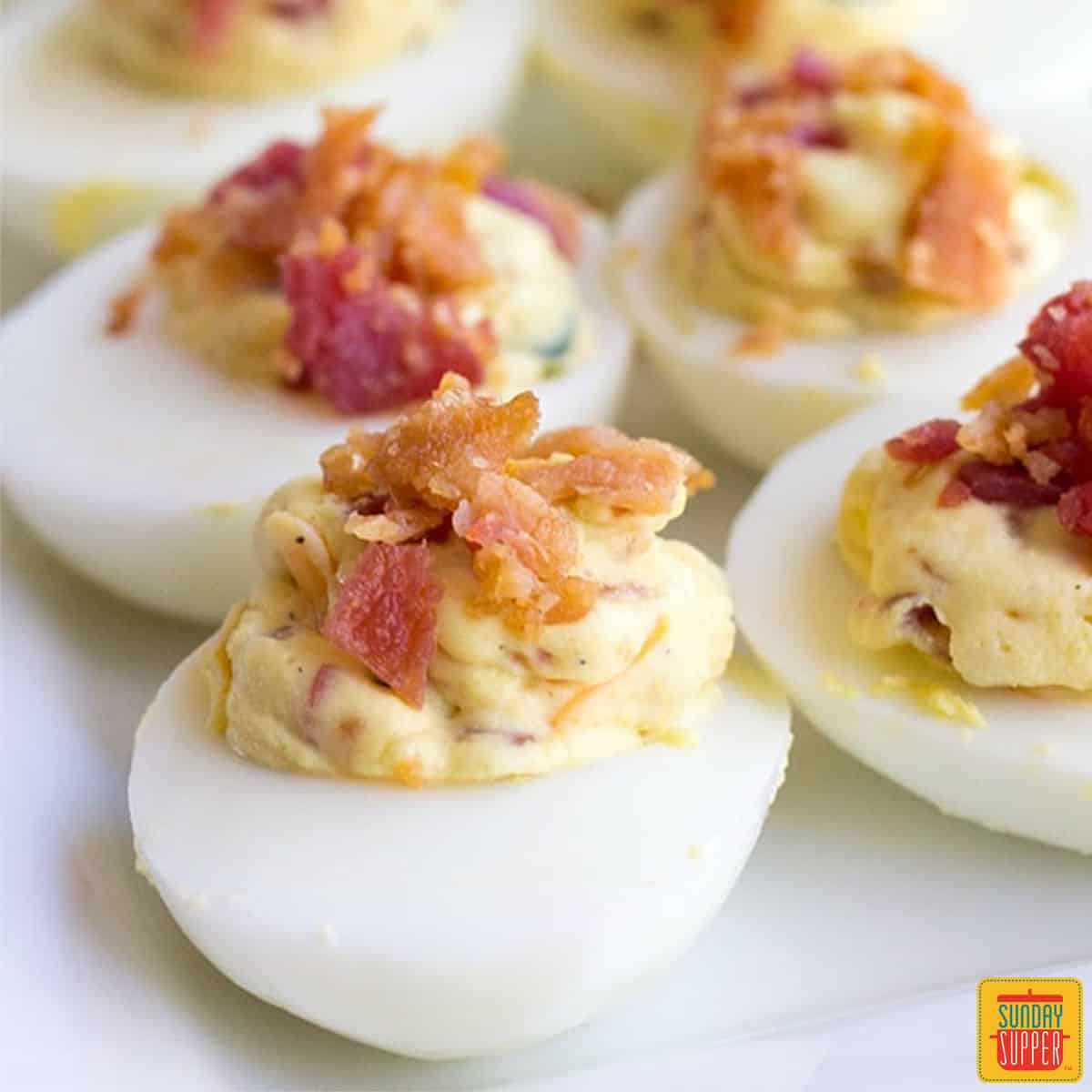 Four jalapeno deviled eggs topped with bacon