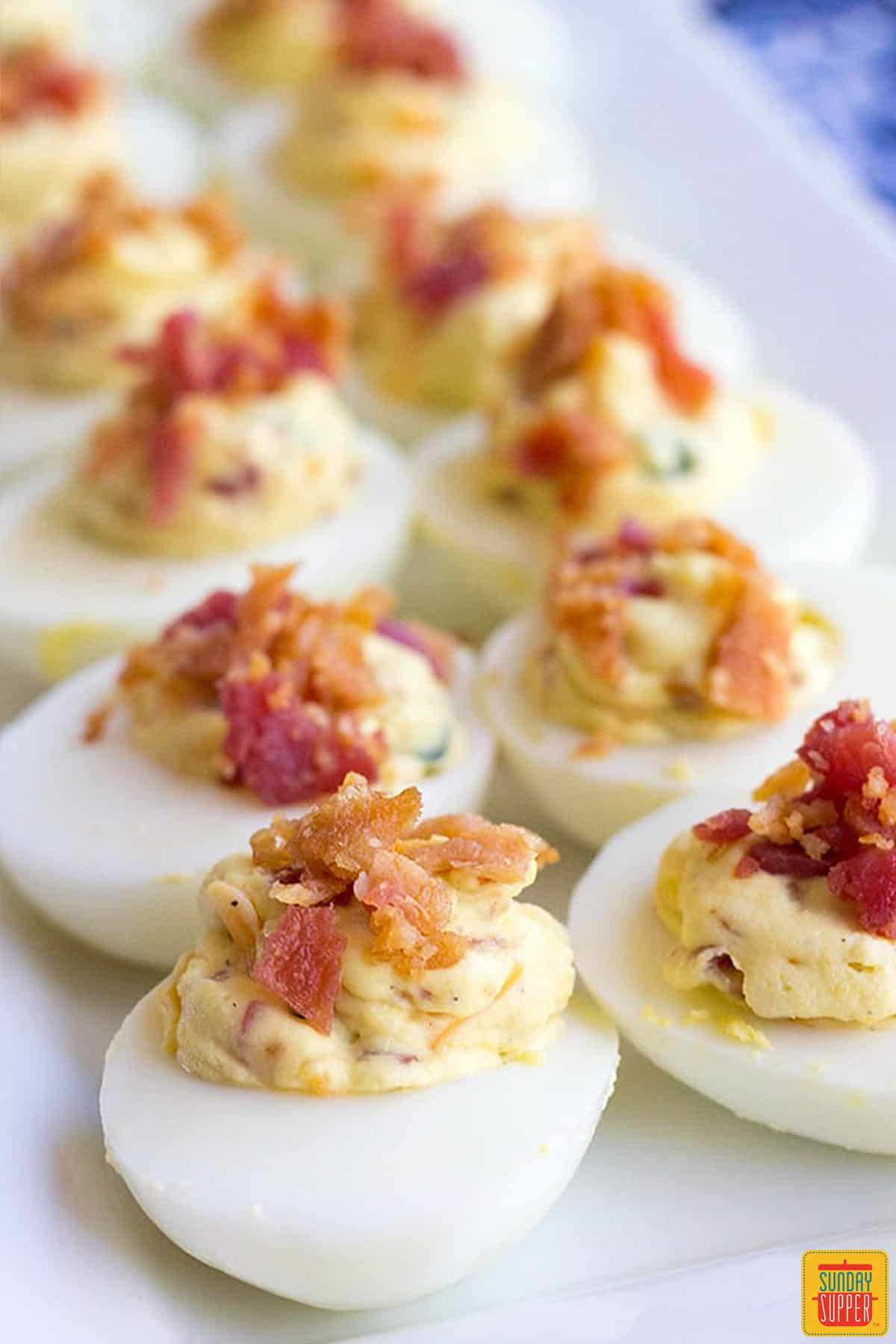 Two rows of bacon jalapeno deviled eggs with cream cheese topped with bacon bits