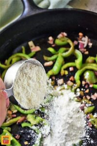 Adding flour to the vegetables in the cast iron skillet