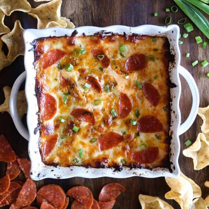 Pepperoni pizza dip in a white dish surrounded by pepperoni, chips, and onions