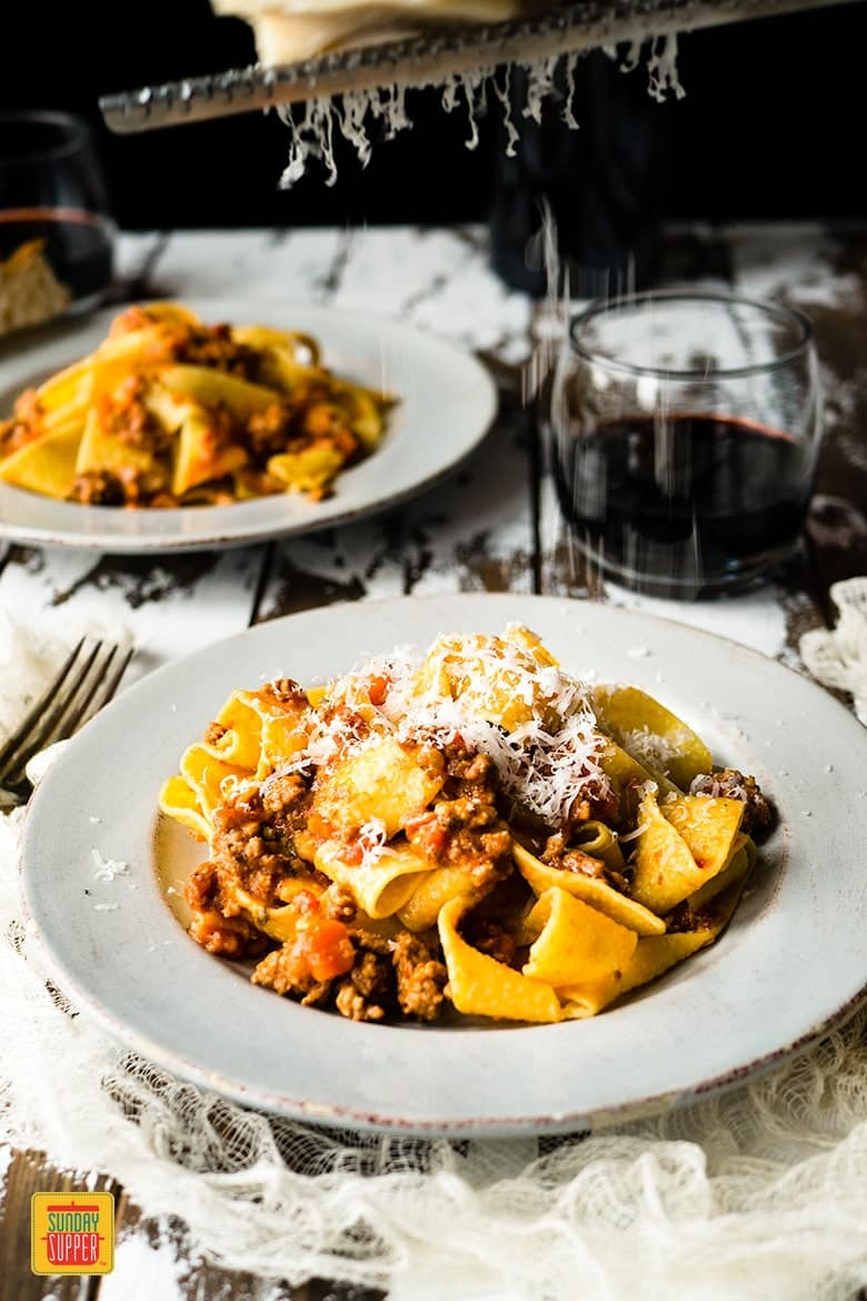 Close up of pappardelle pasta with bolognese sauce in a white dish topped with cheese