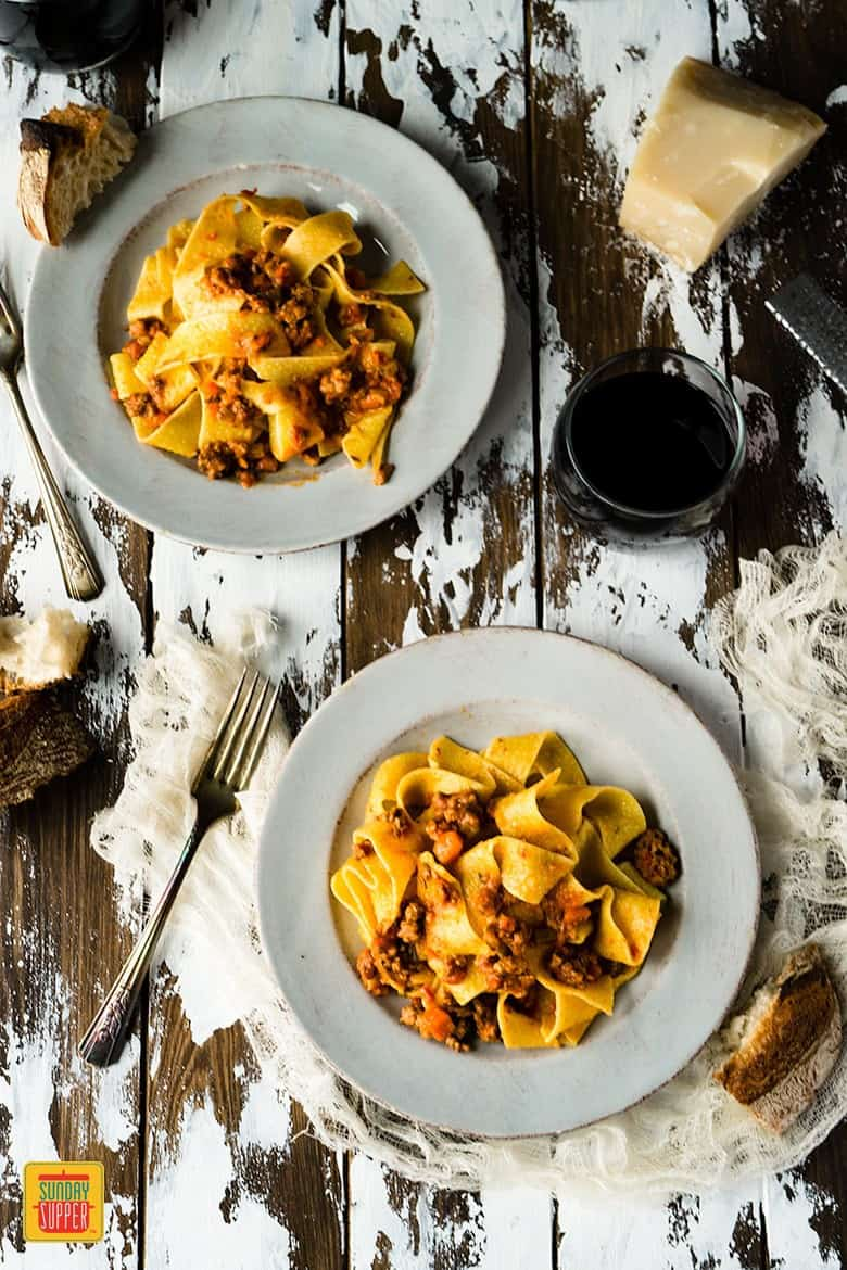 Two off-white plates of pappardelle pasta with homemade bolognese sauce on a distressed wooden surface with a fork, crusty bread, and red wine in a glass