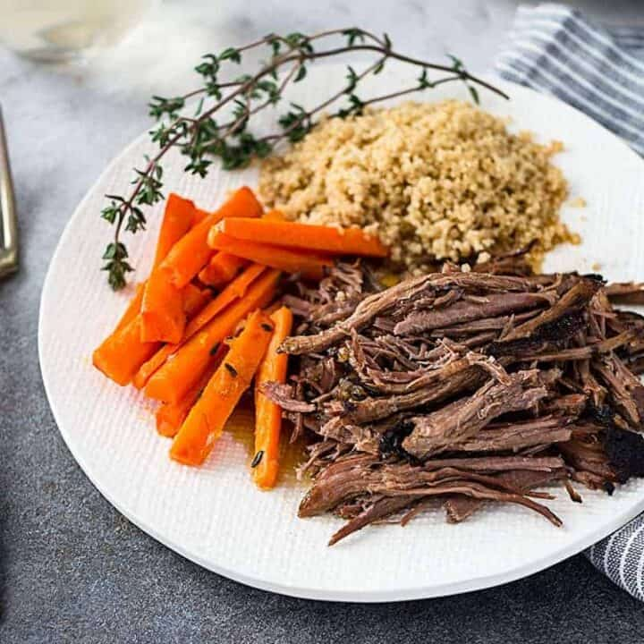 A white plate of slow cooker roast beef with glazed carrots and couscous