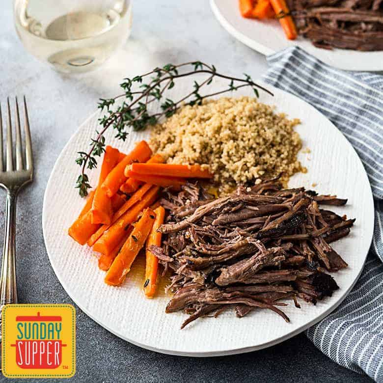 Slow cooker roast beef shredded with carrots and quinoa on a white plate with a fork and blue and white striped towel