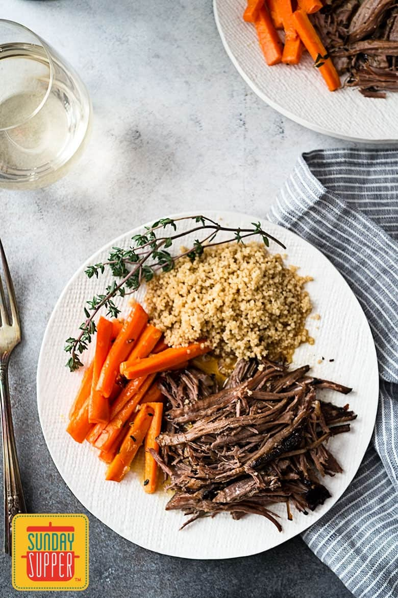 Top down shot of slow cooker roast beef on a white plate with glazed carrots and couscous