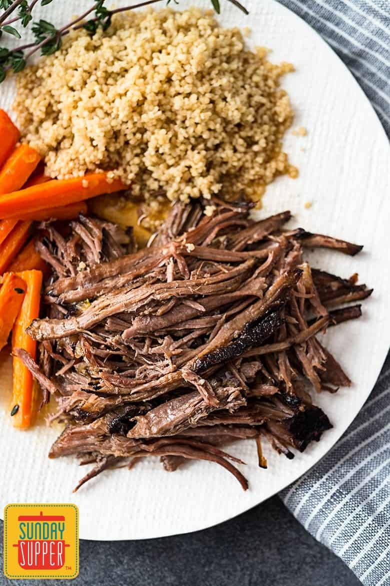 Shredded slow cooker beef on a white platter with carrots and quinoa