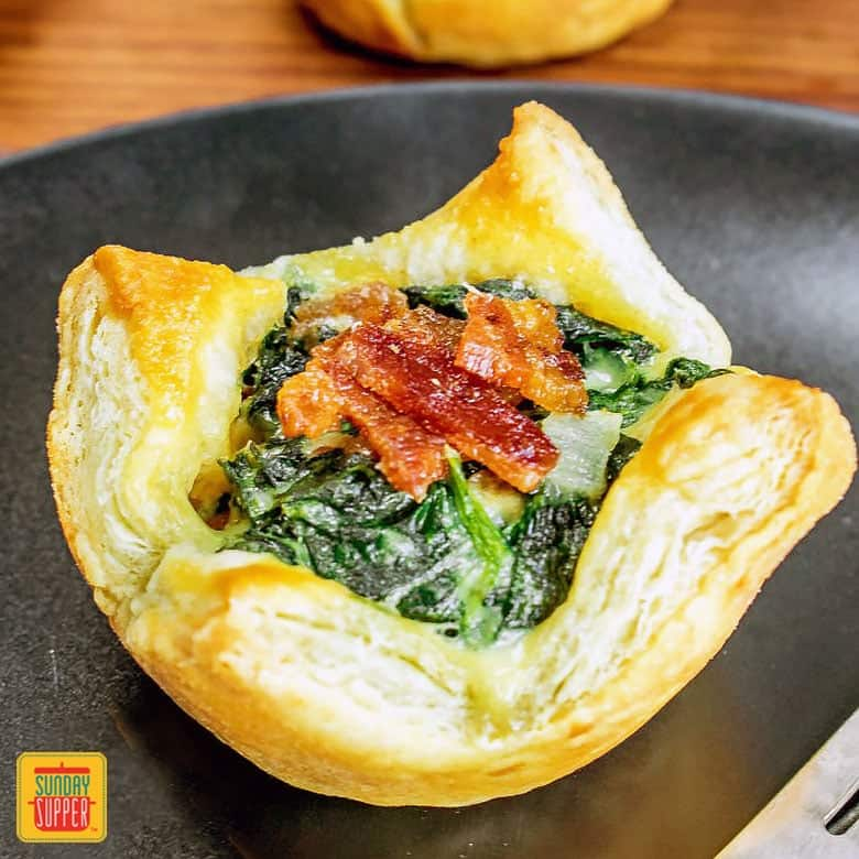 A spinach puff pastry on a black plate with bacon and spinach on top