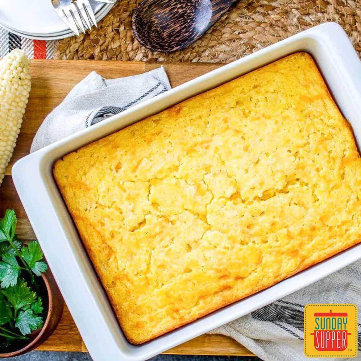 baked creamed corn casserole in a white dish