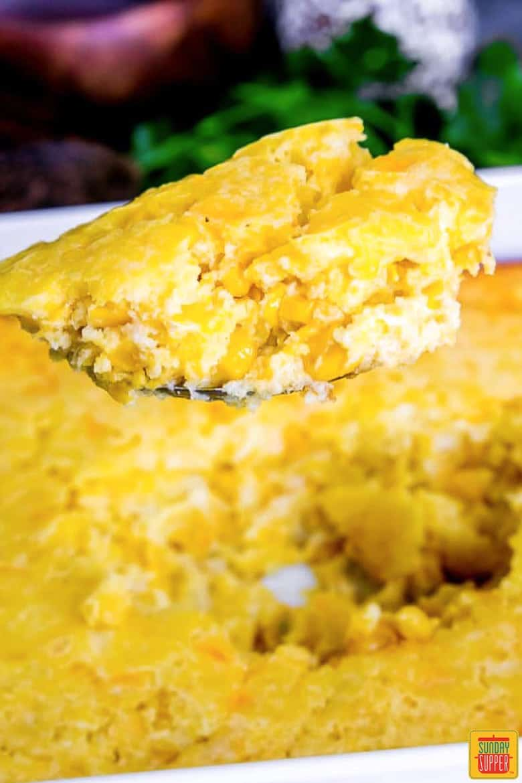 A bite of creamed corn casserole in a serving spoon