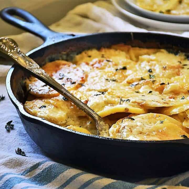 Gluten free au gratin potatoes in a skillet on a towel