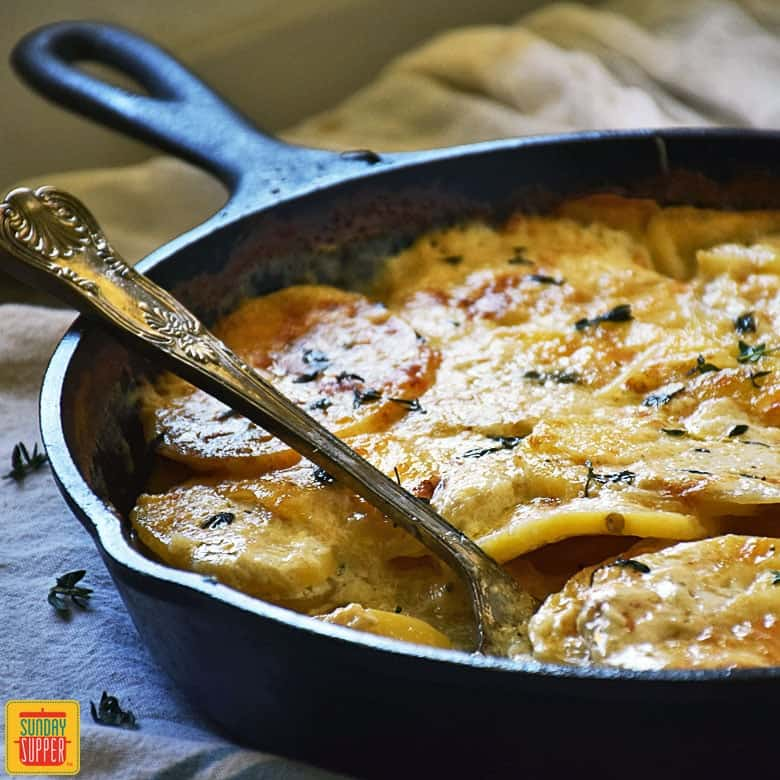 Gluten free potatoes au gratin in a cast iron skillet with a serving spoon