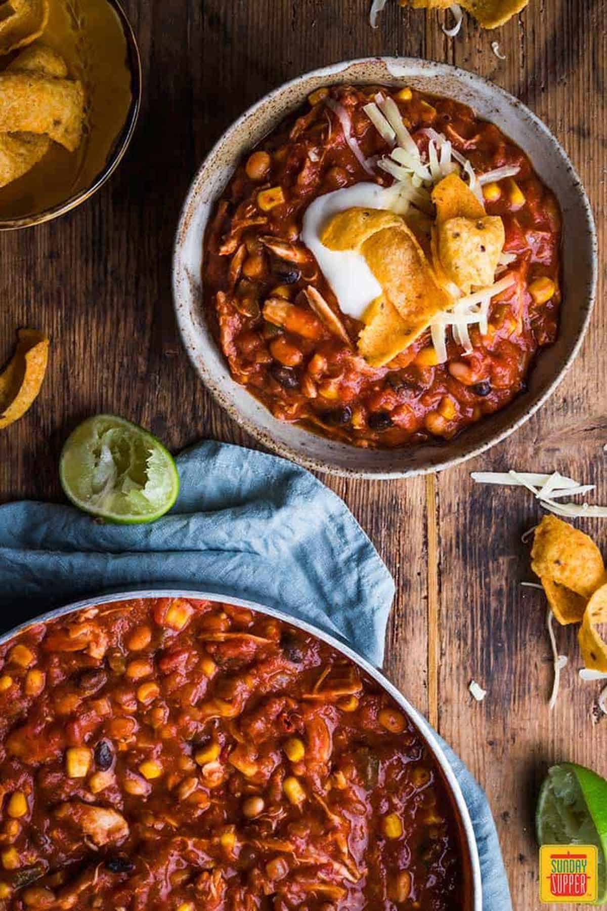 A bowl of chicken chili next to the skillet of chili