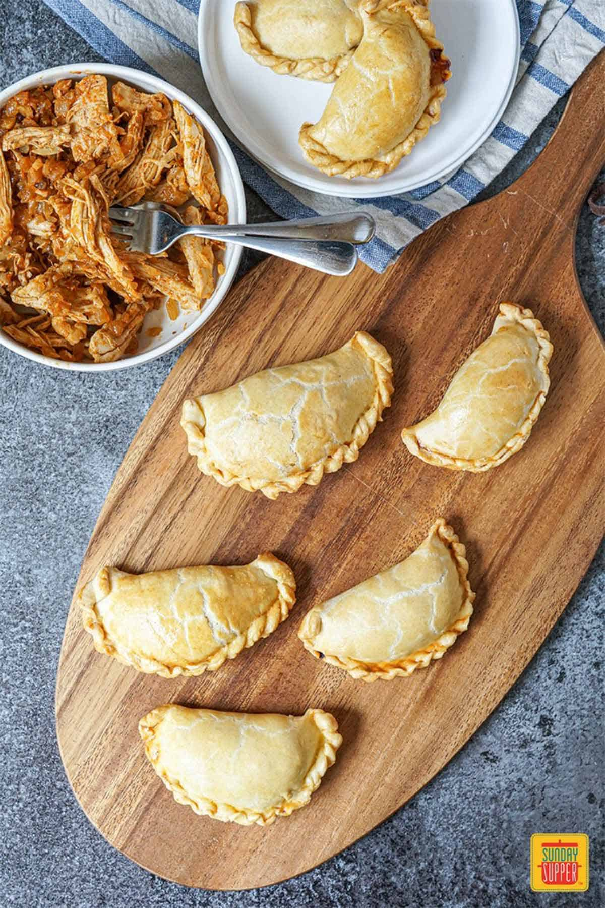 A wooden serving board of five chicken empanadas - make ahead freezer meals
