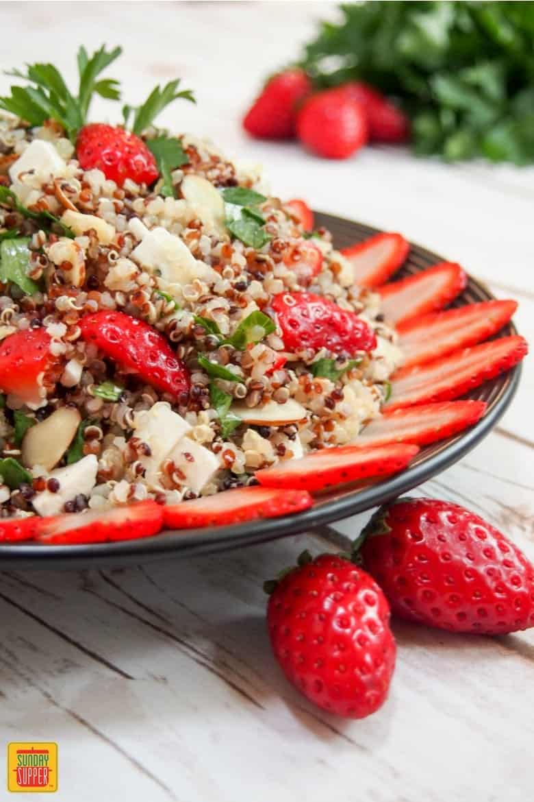 strawberry quinoa salad in a black bowl with two strawberries to the side
