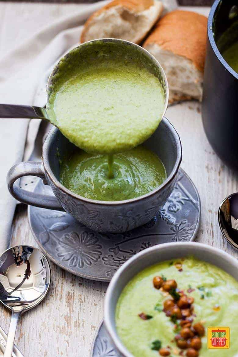 Ladling Easy Broccoli Soup into a cup set on a saucer