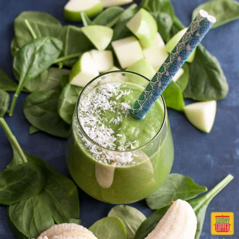 Green apple smoothie in a glass with shaved coconut and fresh apples