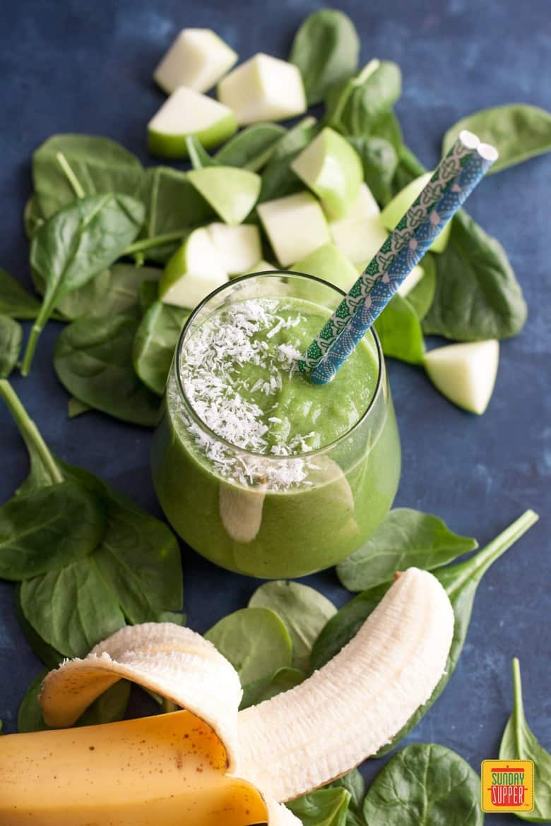 Green Apple Smoothie in a glass topped with shaved coconut by a fresh banana