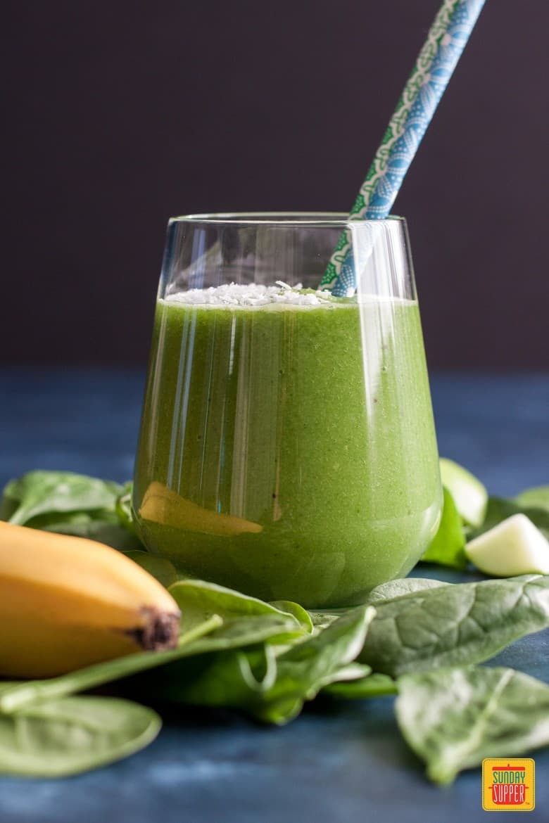 Green breakfast smoothie recipe on a bed of spinach in a glass