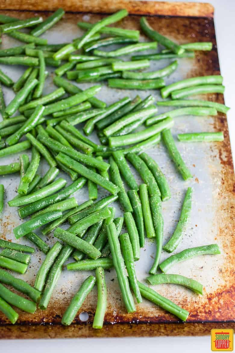 Sheet pan of green beans ready to be roasted in the oven for a tasty side dish