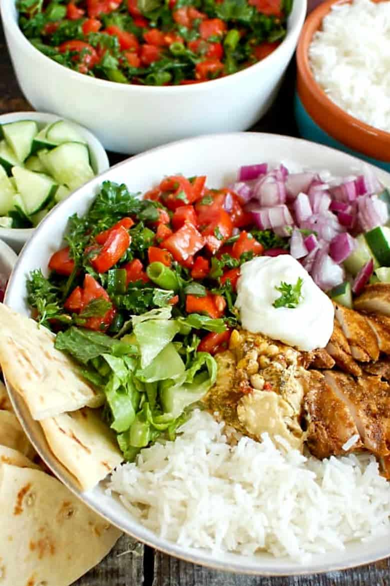 Chicken shawarma bowl over rice in a white bowl