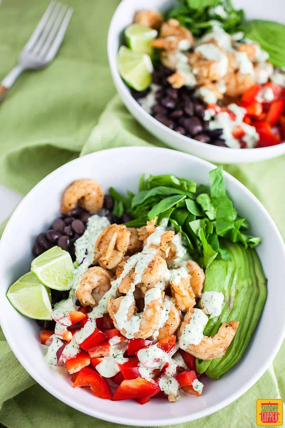 Two bowls of Shrimp Mexican Rice bowl on a green tablecloth