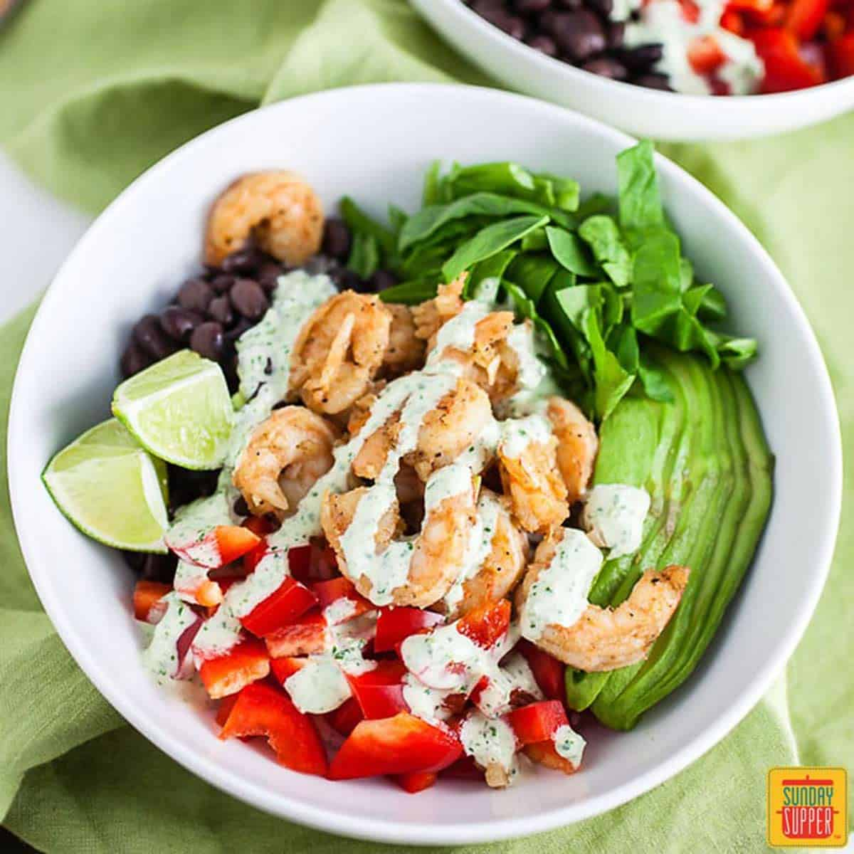 Shrimp Mexican rice bowl in a white bowl with cilantro lime dressing on top