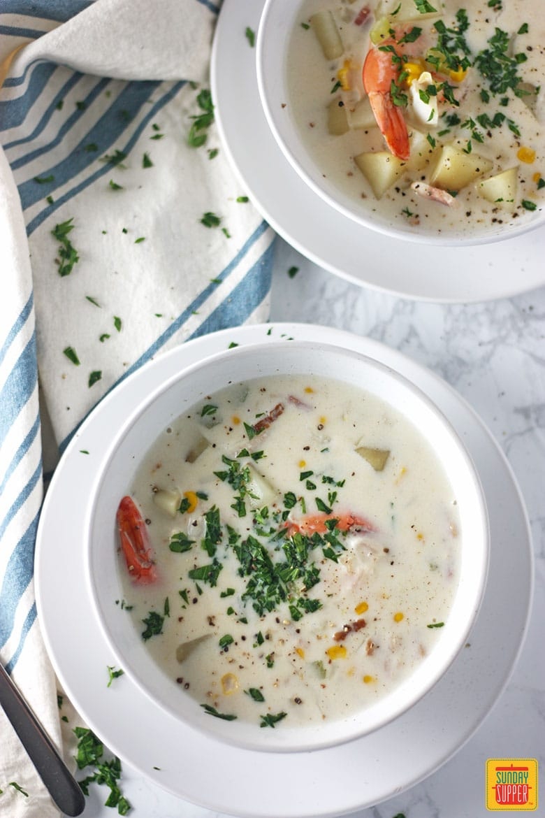 Seafood Chowder recipe with parsley in two white bowls ready to eat