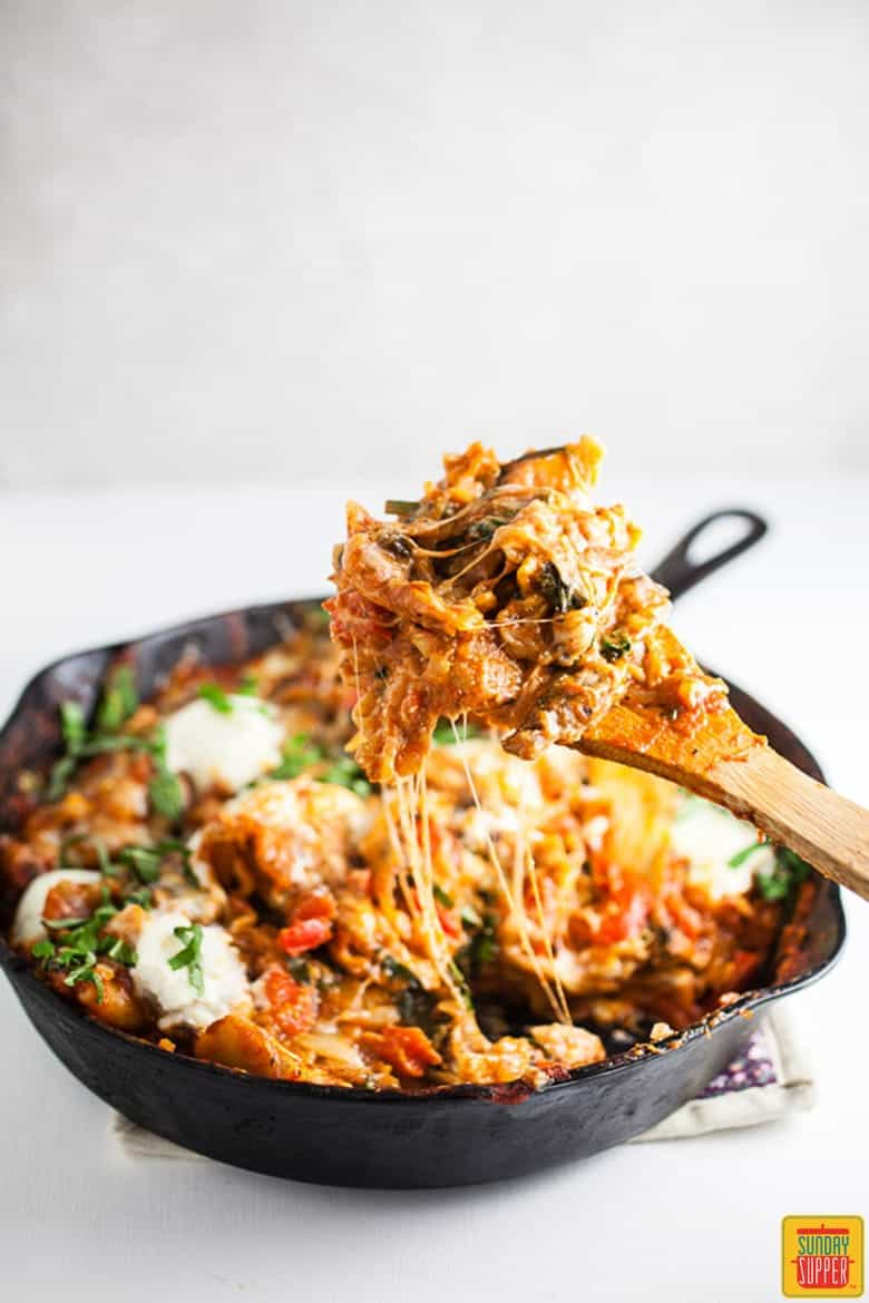 Vegetarian skillet lasagna in the skillet with a wooden spoon