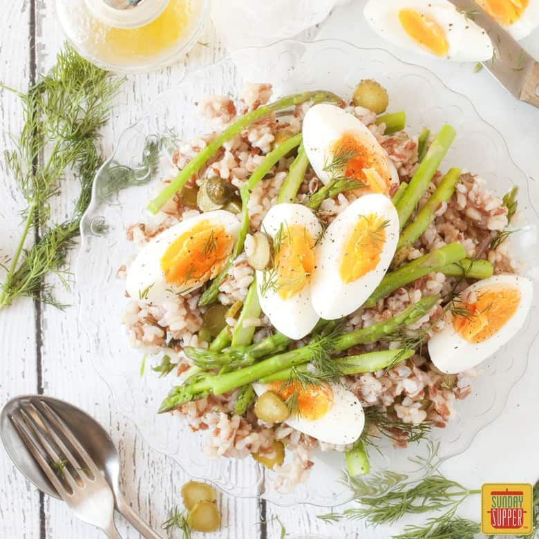 Asparagus Salad with rice topped with boiled eggs on a clear plate