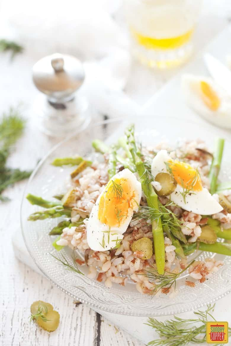Asparagus Salad with rice topped with boiled eggs on a serving plate ready to eat