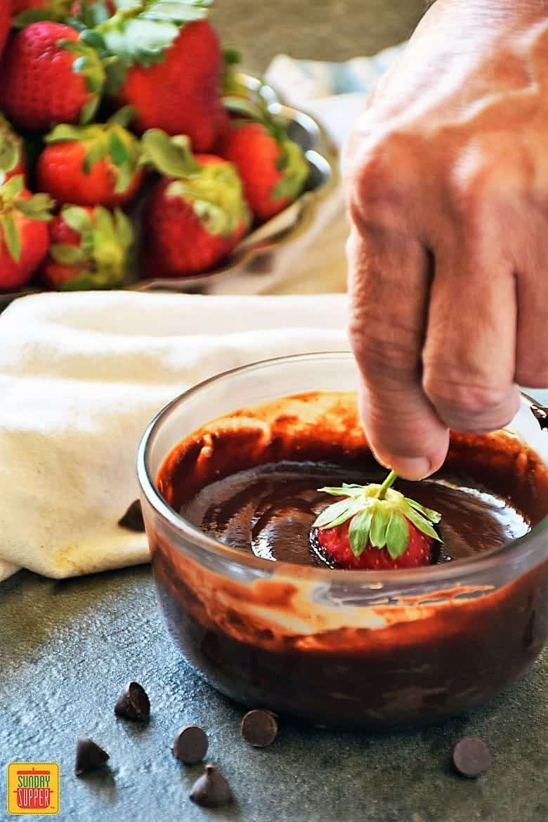 Dipping a plump red strawberry into the smooth chocolate ganache