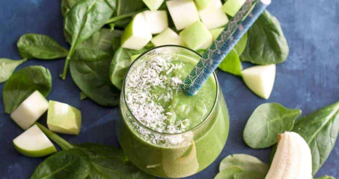 Green apple smoothie surrounded by fresh apple slices