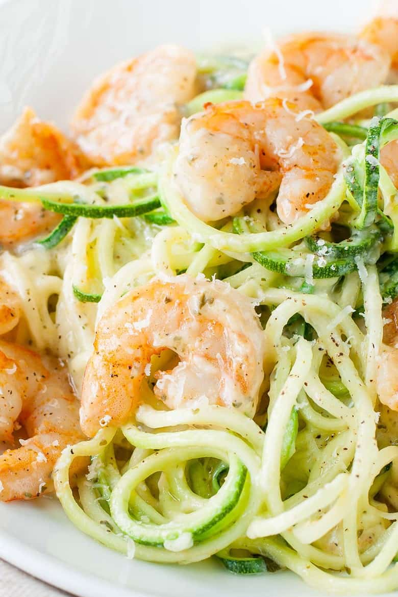 Pesto Parmesan Zucchini Noodles with savory shrimp served on a white plate