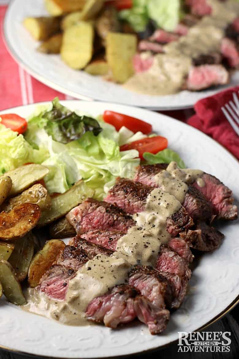 Steak au Poivre with Fingerling Potatoes served on a white plate with a salad