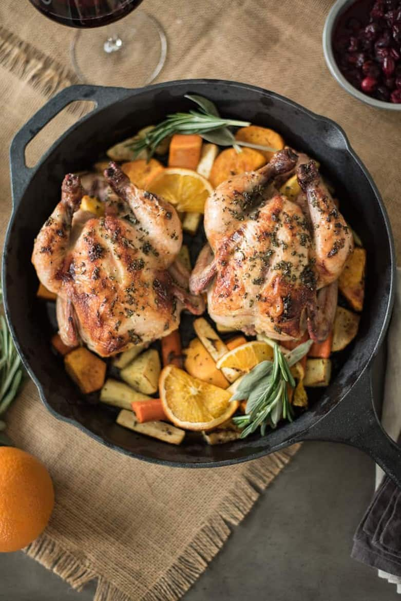 Herb Roasted Cornish Hens with Root Vegetables served in a skillet with oranges