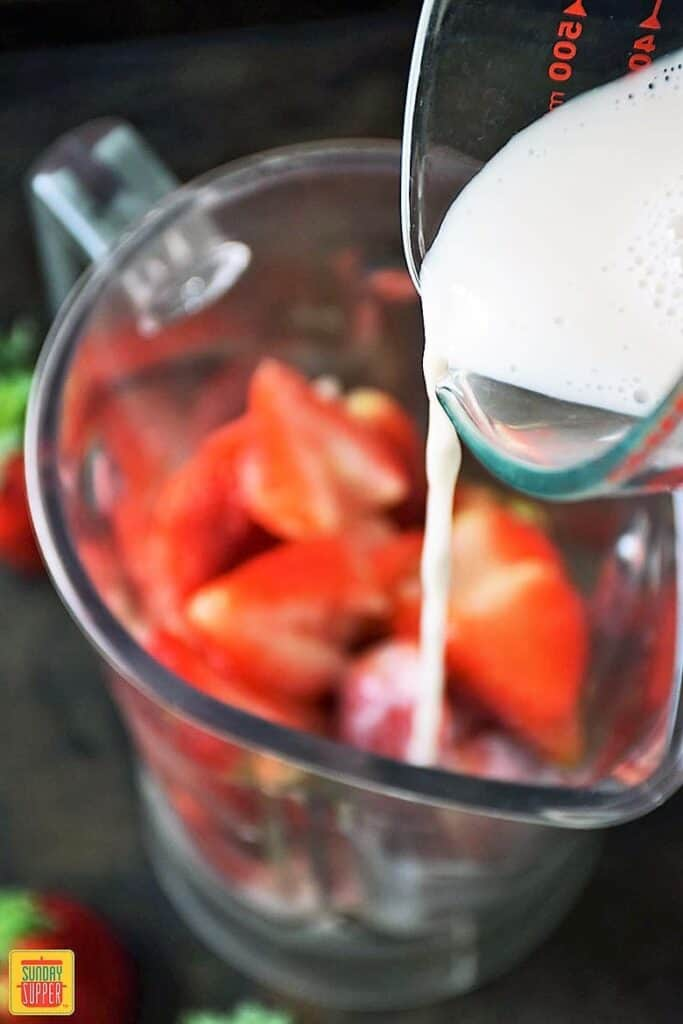 Pouring almond milk into blender with the fresh strawberries