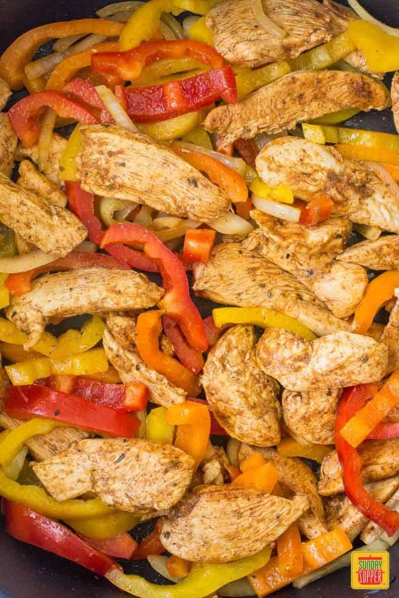 A skillet of chicken and peppers for chicken fajita meal prep bowls.