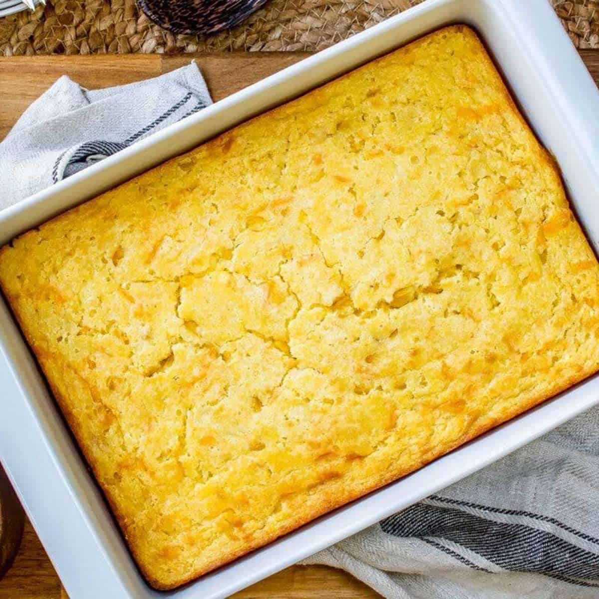 Close up of baked creamed corn casserole in a white dish