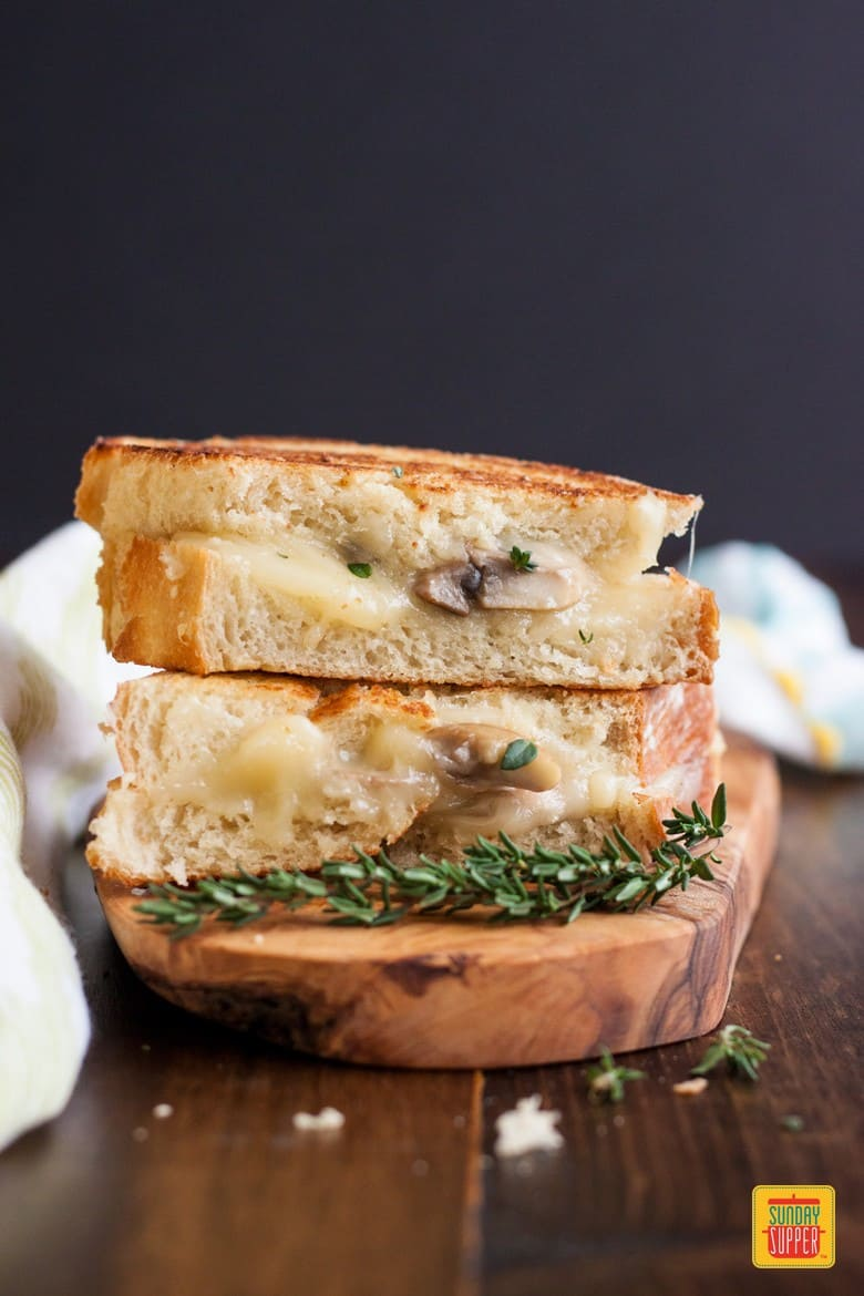 2 halves of a mushroom grilled cheese sandwich stacked on on top of the other with melted cheese and fresh thyme sprigs