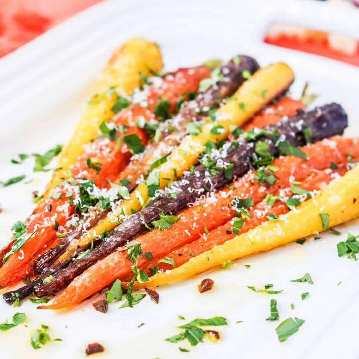 Garlic parmesan roasted carrots on a white plate for Easter side dishes