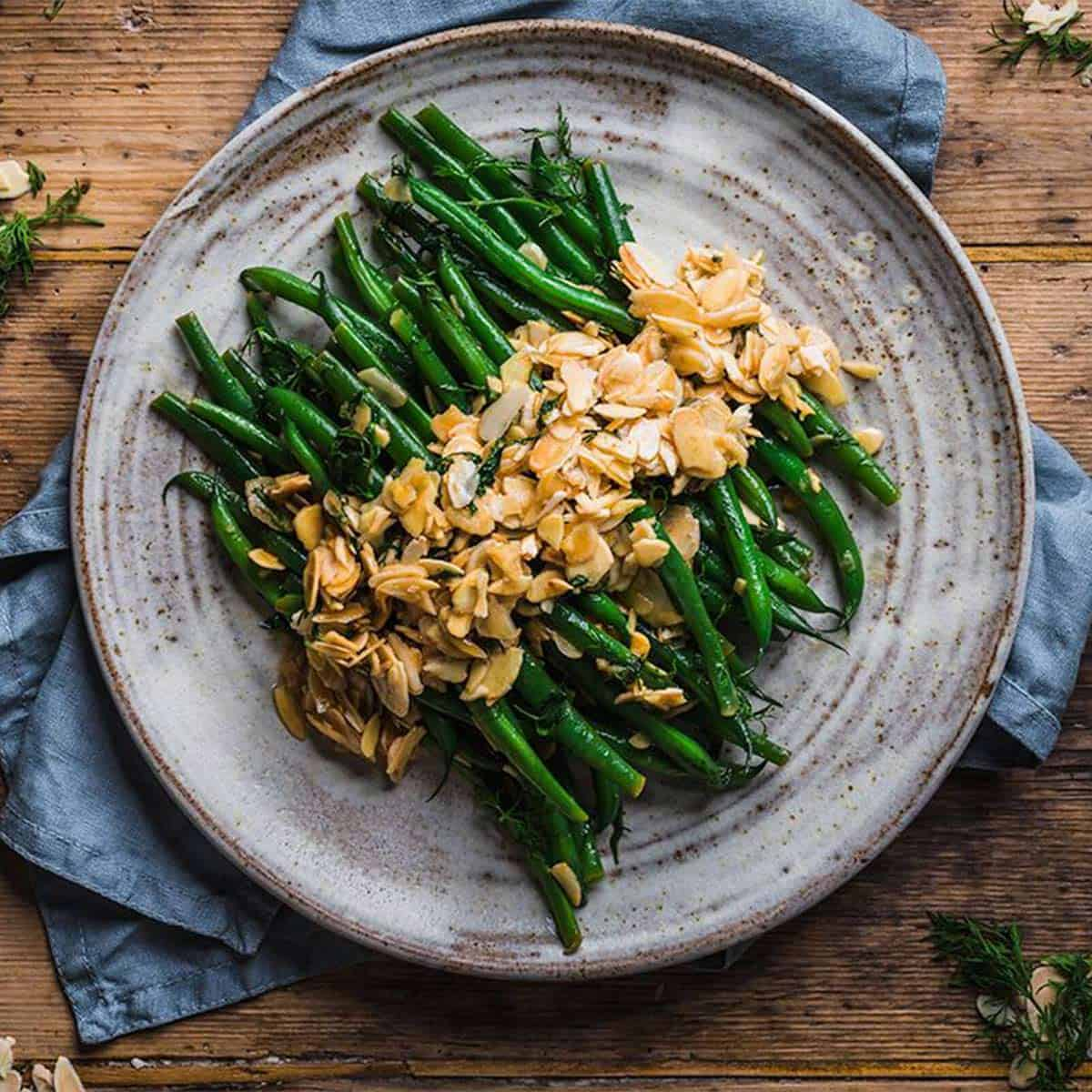 Green bean almondine on a grey speckled plate for Easter side dishes