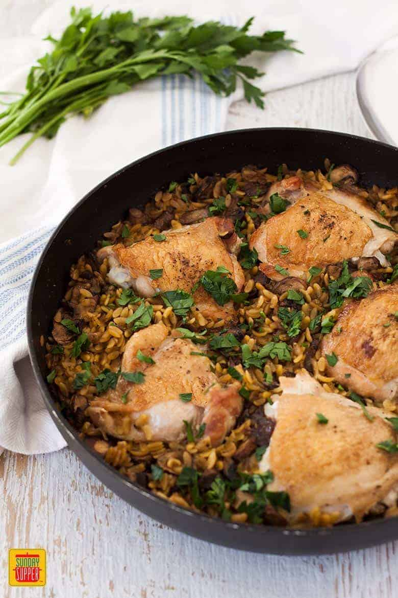 One Pot Chicken Orzo Pasta with Mushrooms in a black skillet with fresh herbs on top
