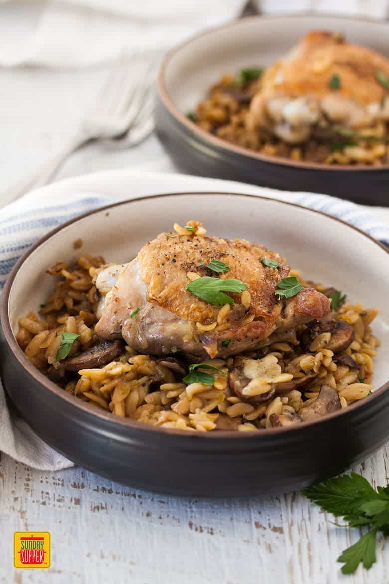 2 black serving bowls of One Pot Chicken Orzo Pasta with Mushrooms