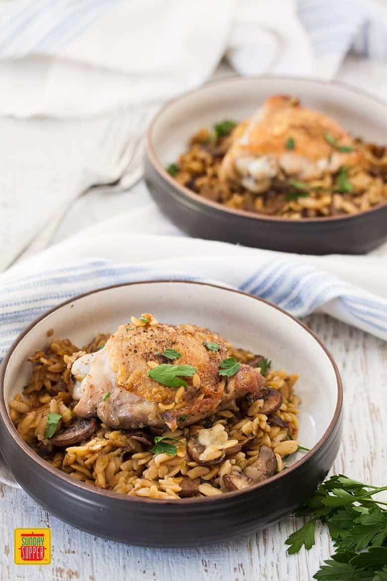 Two bowls of chicken thighs with orzo and mushrooms
