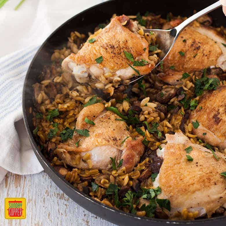 Lifting a piece of chicken thigh out of a skillet with a serving spoon - one pot chicken orzo pasta