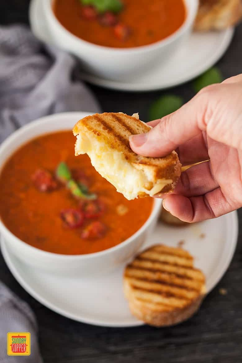 Bowl of Roasted Tomato Soup with hand picking up Mini Grilled Cheese and holding over bowl