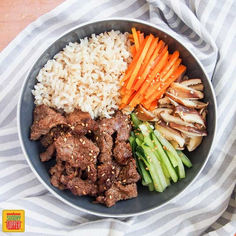 beef bulgogi meal prep bowl set on a striped blue table cover