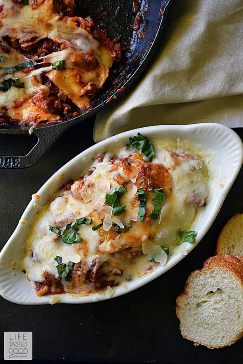 Cheesy Baked Ravioli Skillet in a small white casserole dish next to bread