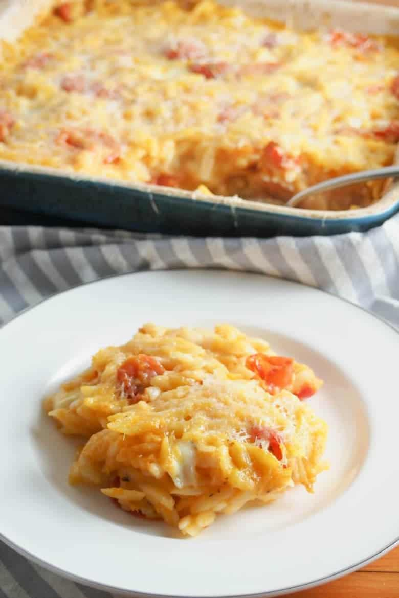 Cheesy orzo pasta bake on a white plate in front of the casserole dish